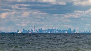 """Ao se aproximar de barco ao litoral notamos a cidade """"emergindo"""" da água. Este efeito é resultado da curvatura da Terra esférica"""