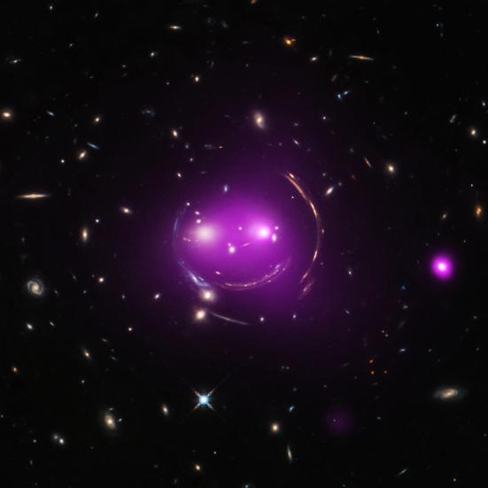 """SDSS J103842.59+484917.7 ou simplesmente """"gato sorridente"""" é um grupo de galáxias que tem uma semelhança de um felino sorrindo. Ela é dominantemente formada por 2 elípticas, cercada por quatro arcos, formado por galáxias ao fundo. Esses arcos aparecem devido ao efeito de lentes gravitacionais. Cada """"galáxia-olho"""" visto é a galáxia mais brilhante do grupo que está indo em direção a outra numa velocidade de 480 milhões de Km/h. Está a 4,6 bilhões de anos-luz de distância da Terra. Fonte: http://chandra.harvard.edu/photo/2015/cheshirecat/ e o artigo, no final: http://arxiv.org/pdf/1505.05501v1.pdf. Fonte: Judy Schmidt"""
