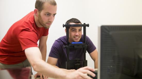 Mark Mills (à esquerda), um estudante de pós-graduação no Centro para o Cérebro, biologia e comportamento, configura um computador trilha olho como parte de um estudo. Crédito: Craig Chandler | Comunicações universitários