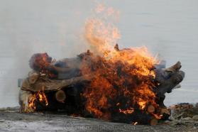 Ao longo da costa de um corpo queima do crematório Harishchandra no rio Ganges em Varanasi, na Índia. Apenas acima do rio um homem seca as roupas que ele apenas lavados no Ganges no calor de uma pira funerária. O Harishchandra Ghat (também conhecido como o Harish Chandra Ghat) é o menor e mais antigo dos dois locais de cremação primárias em Varanasi, às margens do rio Ganges. Imagem: ©Peter Menzel